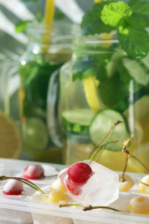 Cold drink of citruses, cucumbers and mint in glass cups, ice with cherries on a wooden table, detox water, home cooking, healthy food Reklamní fotografie