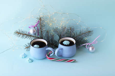 Merry Christmas, two cups of coffee, meringues, festive decor, illumination, mint color background, concept of home comfort and congratulations on winter holidays
