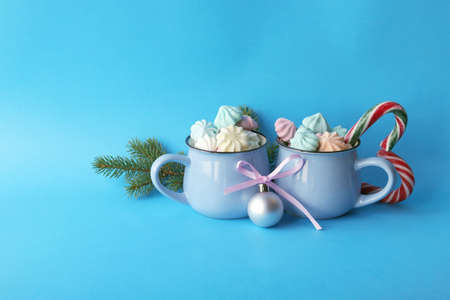 Merry Christmas, two cups of coffee, meringues, spruce branches, festive decor, illumination, blue color background, winter holidays congratulations concept Archivio Fotografico