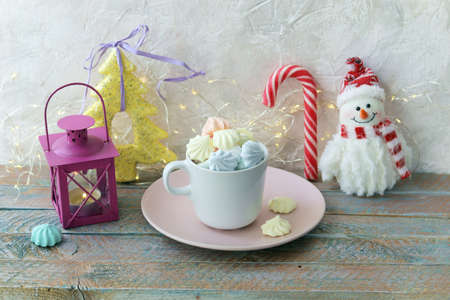 Merry Christmas, a cup of coffee with meringues and caramel, a lantern with a burning candle, festive decor, wooden light background, the concept of home comfort, congratulations on the winter holiday