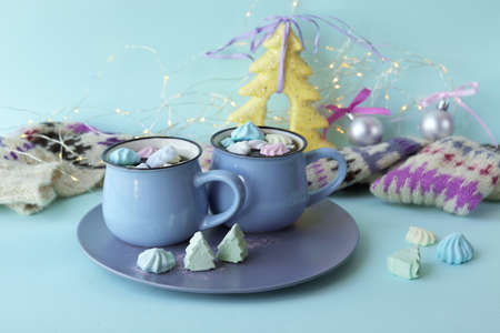 Merry Christmas, two cups of coffee with meringue, a warm scarf, decor, mint color background, the concept of home comfort and congratulations on the winter holidays 版權商用圖片