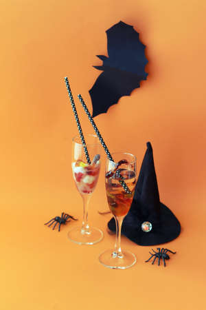 Halloween drinks, dessert with jelly worms, decor on a bright background, mystical cocktail for home party, greeting card, space for lettering Stock Photo