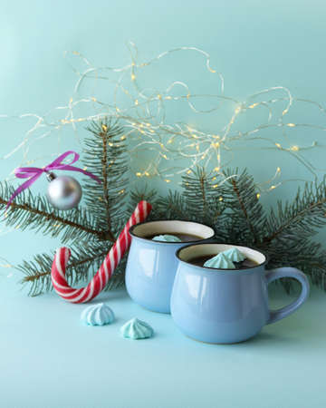 A couple of cups with coffee with meringues, Christmas decor, illumination on a light background, the concept of home comfort, winter holidays
