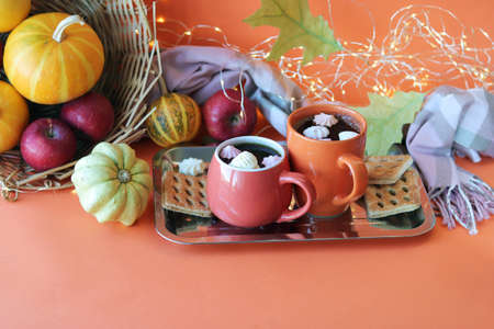 Thanksgiving day, two cups of coffee, meringues, pumpkins, apples, leaves, warm blanket on an orange background, the concept of home comfort, family holidays, autumn season