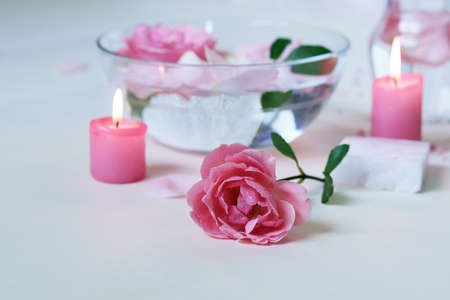 Fresh pink roses, water, petals, candles on a light background, body care products, natural home cosmetics, healthy lifestyle, alternative medicine