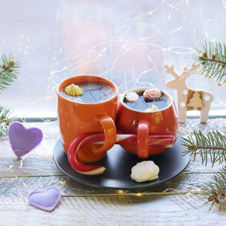Two cups of coffee with meringues, caramel, Christmas decorations, hearts, illumination on a wooden windowsill, the concept of home comfort, love, winter holidays
