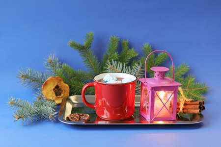 Christmas, a cup of coffee with meringues, spices, a lantern with a burning candle and spruce branches on a blue background, the concept of home comfort, congratulations on the winter holidays