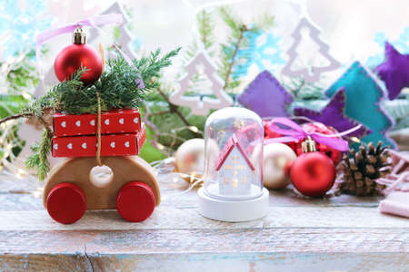 Christmas toy house, wooden car with gifts and a tree, New Year decorations, illumination, fir-tree branches on the background of the window, the concept of home comfort, congratulations, postcard