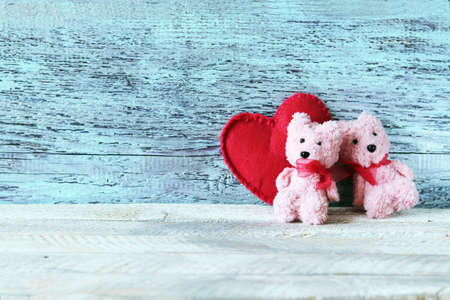 A pair of toys Teddy bears on the background of a big red heart, the concept of congratulations, postcard Banque d'images