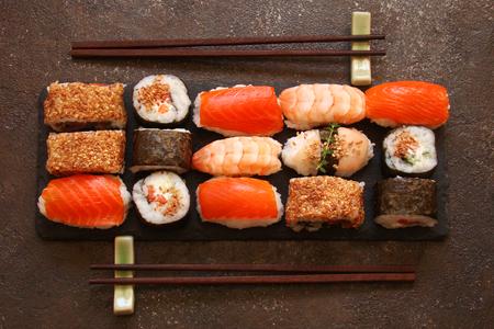 sushi and sushi rolls, sushi nigiri on stone plate on dark background