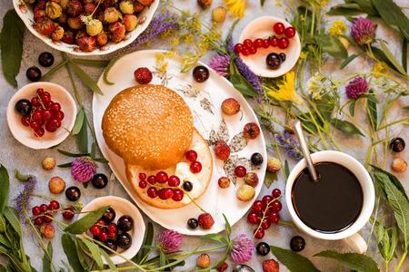 Zomer ontbijt muffin, roomkaas, verse bessen krenten, aardbeien op een houten achtergrond met wilde bloemen Stockfoto