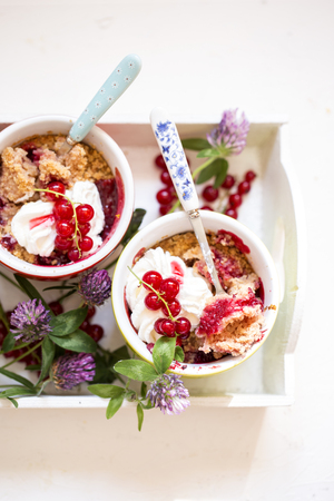 crumble with fresh berries, currants, cherries, strawberries and whipped cream Stock Photo
