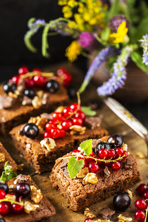 brownie chocolate cake with fresh berries, currants, and mint and nuts