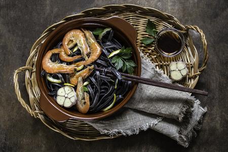 shrimp fried black noodles pasta with lemon, garlic and spices Stock Photo