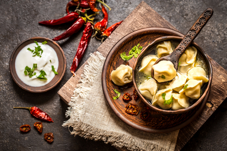Russian dumplings with meat and broth and herbs in a rustic style