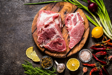 meat fillet of pork with herbs, lemon and spices on a wooden Board