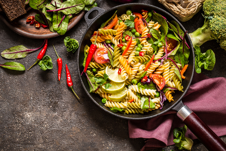 pasta salad with fresh herbs spinach, vegetables and green peas, spicy pepper