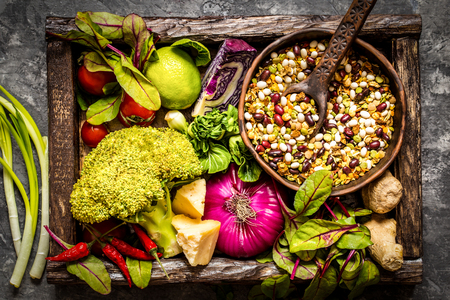 Fresh fruit, vegetables, cereals, nuts and greens, the ingredients for a healthy lifestyle, healthy food in a wooden box Stock Photo
