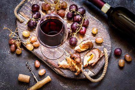 Red wine with grapes, meat, glass a glass on a wooden Board in a rustic style