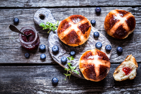 Easter hot cross buns on a wooden background with a jar of jam and fresh berries blueberry rustic