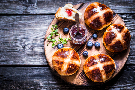 Easter hot cross buns on a wooden background with a jar of jam and fresh berries blueberry rustic Stock Photo - 93954130