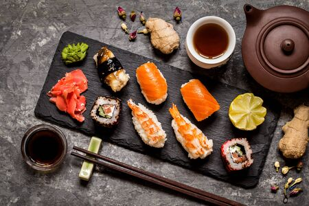 sushi and sushi rolls, sushi nigiri on stone plate on dark background, mustard wasabi, and ginger 版權商用圖片 - 94181635