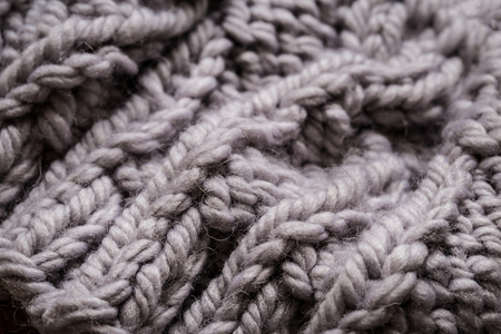 Knitting gray wool, chunky knit with balls on wooden background