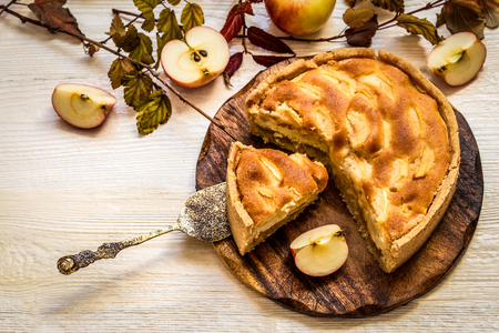 Apple pie on wooden chopping Board on white background