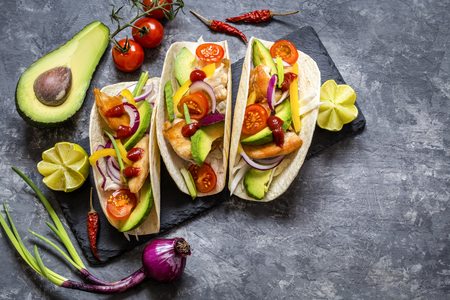 Mexican food tacos, fried chicken, greens,  avocado, pepper, red cabbage and avocado in tortillas on dark background