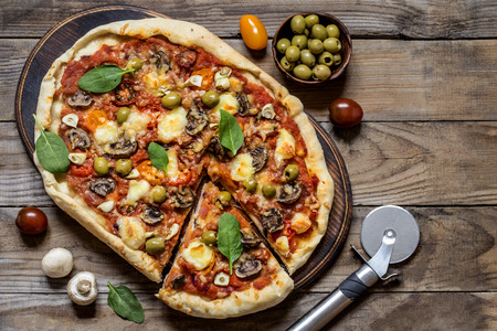 pizza with mushrooms, tomatoes, olives and spinach and goat cheese on wooden background