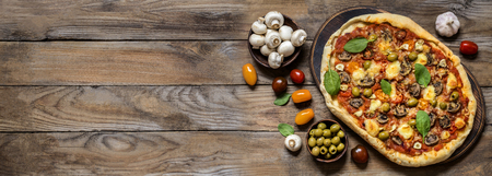 banner for advertisement pizza with mushrooms, tomatoes, olives and spinach on wooden background 版權商用圖片 - 124138354
