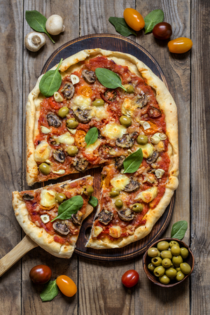 pizza with mushrooms, tomatoes, olives and spinach and goat cheese on wooden background 版權商用圖片 - 124138302
