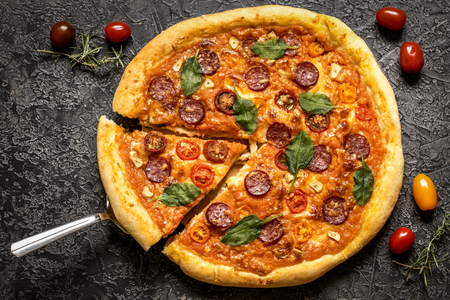 pizza with salami sausage, spinach and cherry tomatoes and tomato sauce on a dark background 版權商用圖片