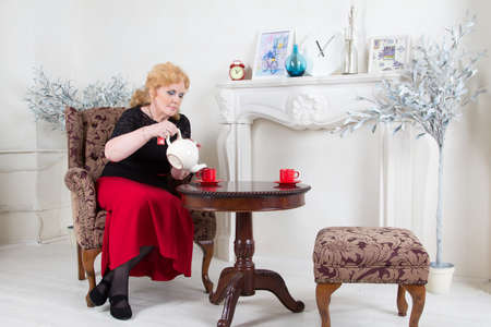 cosily: Seated in a chair adult woman pours tea Stock Photo