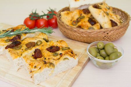 Freshly baked traditional Italian focaccia bread with green olives and sun-dried tomatoes, selective focus Stock Photo