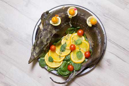 sturgeon: Sturgeon with oranges, spinach, cherry tomatoes and physalis . Baked whole. Selective focus. Stock Photo