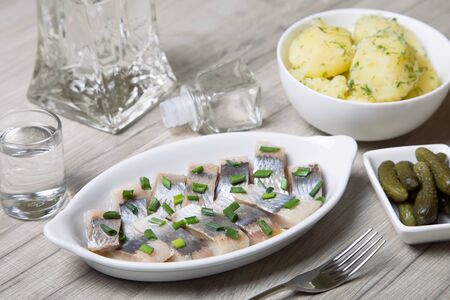 marinated gherkins: Pieces of herring with onions, gherkins, boiled potatoes and vodka. Selective focus Stock Photo
