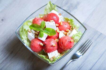 Salad with feta cheese, watermelon and pine nuts. Close-up. Selective focusing.