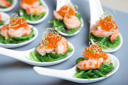 Apéritif à base de chuka d'algues, de crabes et de caviar sur des spoos portionnés. Mise au point sélective, gros plan. Banque d'images
