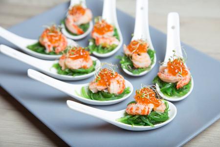 Apéritif à base de chuka d'algues, de crabes et de caviar sur des spoos portionnés. Mise au point sélective, gros plan.
