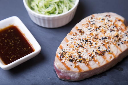 Grilled tuna with sesame and cucumber salad on a black board. Close-up, selective focus.