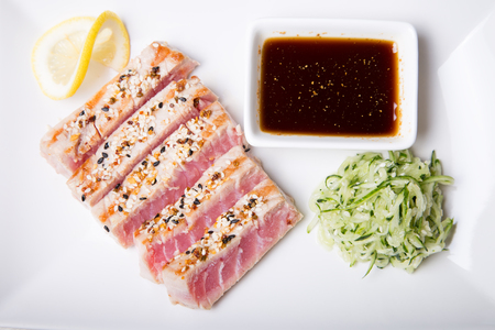 Grilled tuna with sesame seeds and cucumber salad on a white plate. Close-up, selective focus Фото со стока