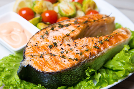 Grilled salmon with brussels sprouts and tomatoes. Close-up, selective focus.