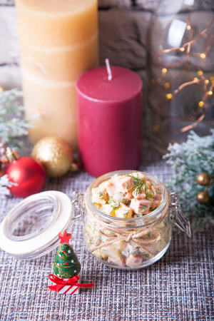 Traditional New Year and Christmas Russian salad Olivier (olivie) in a jar. Close-up, selective focus.