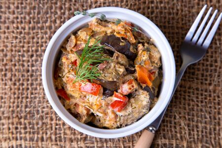 Eggplants with tomatoes, bulgarian red (sweet) pepper, onion, dill and sour cream. Vegetarian dish. Close-up.