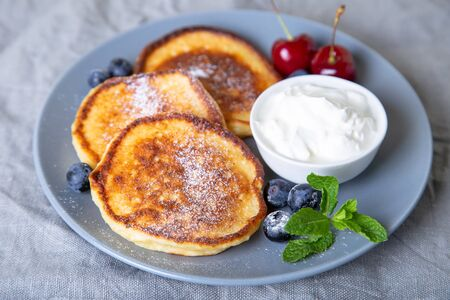 Cottage cheese pancakes (syrniki). Homemade cheesecakes from cottage cheese with sour cream and berries. Traditional Russian dish. Close-up. Zdjęcie Seryjne