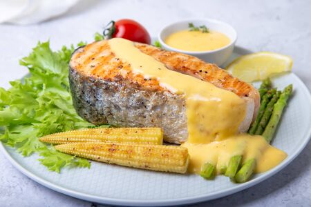 Grilled salmon with asparagus, corn mini and hollandaise sauce. Close-up.