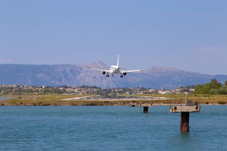 Passenger's airplane is landing at Kerkyra Airport. Greece, Corfu island. Decrease in height, close-up. Runway on the background of mountains and sea.