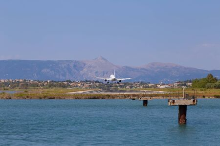 Passenger's airplane is landing at Kerkyra Airport. Greece, Corfu island. Decrease in height. Runway on the background of mountains and sea.