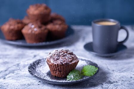 Chocolate muffins with mint on a black plate, strewed with icing sugar.